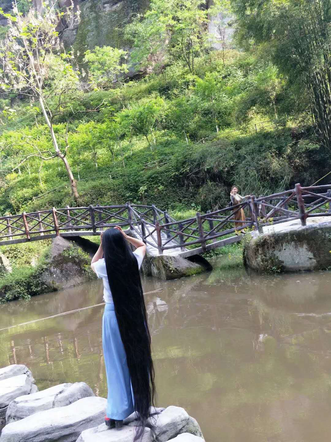 Floor length plus long hair stand near waterfall